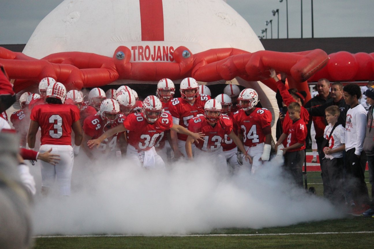 The football team gets ready to run out onto the field to start the game.