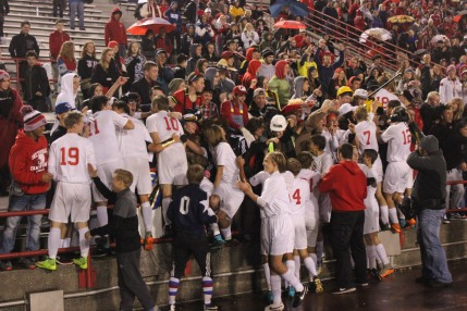 The boys soccer team races to celebrate with the student section after defeating Lafayette Harrison 4-0 in the state game.