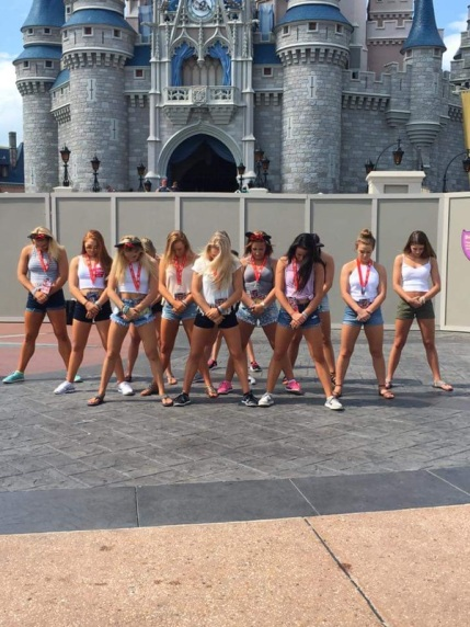 n front of the castle in Magic Kingdom, the team stands in their opening formation of their routine.