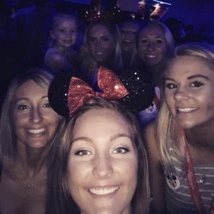 Seniors Danielle Petty, Gwen Feldmeyer, and Allie Armes take a selfie with teammates inside Space Mountain.