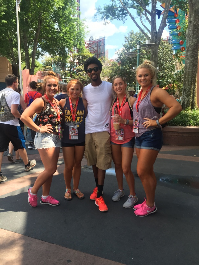 Allie Armes and Danielle Petty pose with teammates before riding a ride.