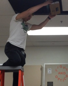Junior Marco Copat prepares to drop his contraption during sixth period physics. It ended up surviving this drop, and moving onto the next height.