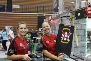 Sophmore Veronica Strange and junior Madison Schnurpel pose for a photo before hanging the robotics battle standard designed by junior Zach Schneider.