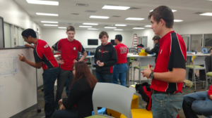 Juniors Akhil Isanaka and Reis Simpson propose design ideas for this year's robot. Senior Max Newport, as well as other team members not visible in picture, listen closely in order to give feedback.
